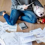 person on floor with bills showing debts owed