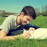 man laying in grass with notepad