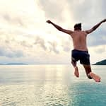 man-jumping-off-cliff-at-sunset