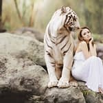woman and a white tiger sitting together on a rock