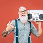 Happy senior man listening to music with boombox outdoor - Crazy hipster male having fun dancing with vintage stereo