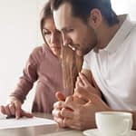 Serious couple studying credit card statement