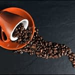 A coffee cup is tiled over spilling out coffee beans.