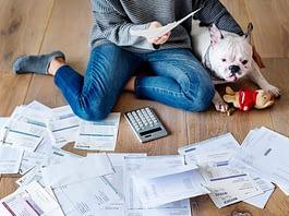 person on floor with bills showing debts owed
