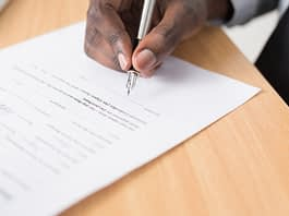 A man signs a document with a pen.