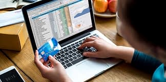 person holding credit card in front of a laptop