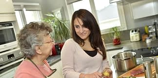 a senior woman and a younger woman conversing in a kitchen