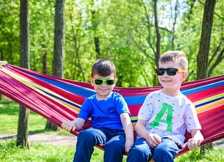 Two sibling brothers with sunglasses relaxing on hammock on warm sunny day in forest or city park. Brothers kid boy having fun together. Friendship concept.