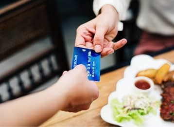 two hands holding a credit card