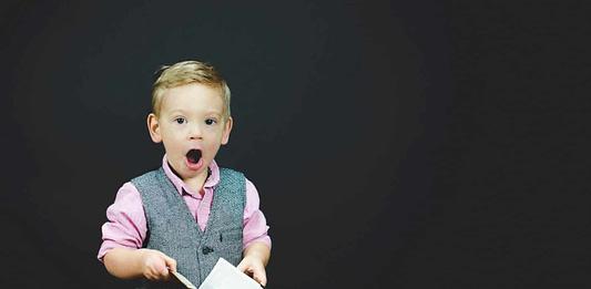 little-boy-holding-book-shocked-look