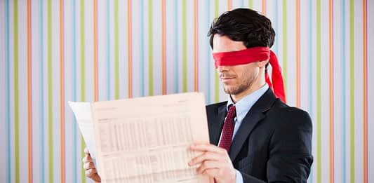young-adult-man-reading-stock-quotes-newspaper-blindfolded