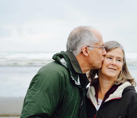 mature-man-kissing-woman-on-beach